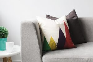 Two pillows rest on grey couch next to a white table. Receive counseling for trauma and PTSD counseling in Beachwood, Ohio 44122. Request an appointment to address depression, anxiety, stress, relationship issues, low-esteem and more.