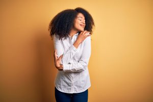 A woman hugging her self. Self-esteem counseling in Beachwood Ohio 44122 is available to you. Feel free from anxiety, depression, stress, poor body image, overeating and more. You can love yourself fully the way you are, because you are amazing. Start today.