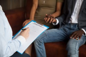 A couple experiencing infertility visiting with a doctor. Grief counseling in Beachwood, Ohio 44122 can help. Symptoms of depression, overeating, anxiety, self esteem, and depression impact grief.