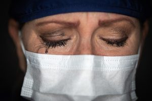 Tearful Stressed Female Doctor or Nurse Wearing Medical Face Mask on Dark Background. PTSD Counseling in Beachwood, Ohio 44122. Help with depression, difficulty sleeping, nightmares, COVID impact.
