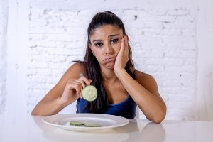 Depressed Dieting Woman Holding Folk Looking At Small Green Vegetable. Emotional eating help. Counseling for women Beachwood, Ohio 44122.