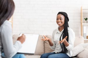Successful therapy. Happy black female patient talking to psychologist at her office, expressing gratitude. Therapy for black girls Cleveland, Ohio 44122. Therapy for depression,. Counseling for anxiety. Online therapy and counseling. Receive help with low-self esteem. Overcome addictive behaviors and impostor syndrome.