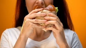 Woman eagerly eating tasty cheeseburger, bad eating habits, unhealthy snack. Get help for emotional eating due to depression and anxiety. Counseling in Cleveland, Ohio 44122. Black therapist. Women's issues. Counseling for self-esteem. Difficulty focusing. Thinking about death. Grieving. Hopelessness, worthlessness. Overcome with therapy.