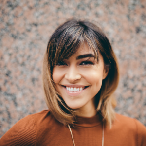 smiling hispanic woman with brunette hair and blonde tips. Wearing a burnt orange top. Individual counseling services online therapy in Ohio 44122. We're located near Cleveland, Ohio. Offer support for depression, anxiety, self esteem, weight management, emotional eating, relationship problems, grief and more. We offer EMDR and trauma therapy.