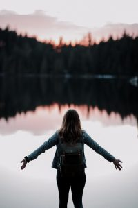 Woman standing on the bank of pond with hands open wide. Counseling for anxiety, depression in Beachwood, Ohio 44122. Online counseling available